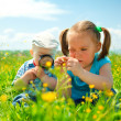 Children are playing on green meadow - Stock Photo