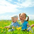 Two children are having fun on green meadow - Stock Photo