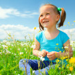 Little girl is playing on green meadow — Stock Photo #5627461