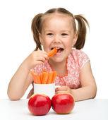 かわいい女の子はニンジンとリンゴを食べる — ストック写真