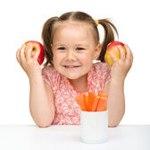 Cute little girl eats carrot and apples — Stock Photo