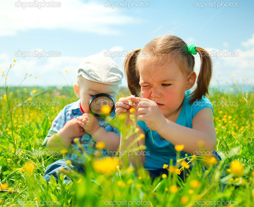 Children are playing on green meadow stock image