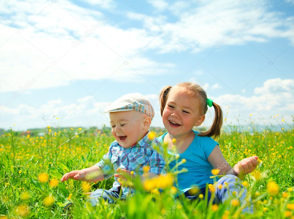 Two children (a girl and a boy) are having fun on green meadow — Stock Photo #5627457