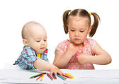 Two children are drawing on paper using markers — Stock Photo