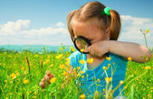 Little girl examining flowers using magnifier — Stock Photo