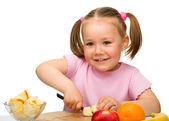 小さな女の子がサラダの果物を切って — ストック写真