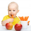 Cute little boy eats carrot and apples — Stock Photo #5993712