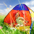 Girl is playing outdoors under tent — Stock Photo