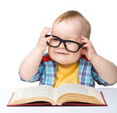 Little child play with book and glasses — Stock Photo