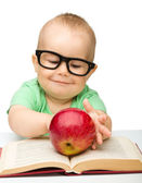 Little child is playing with red apple — Стоковое фото