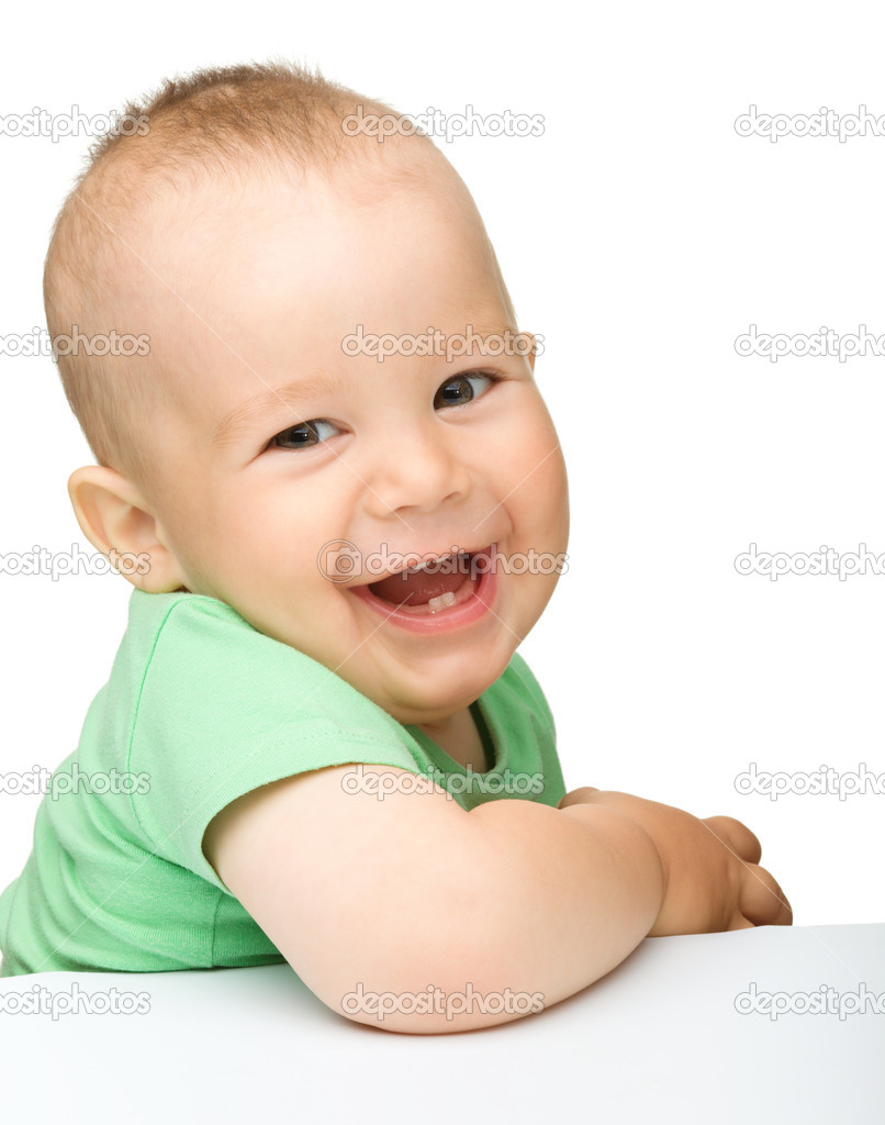 Portrait of a cute cheerful little boy, who is smiling while sitting at table, isolated over white  Lizenzfreies Foto #6005652