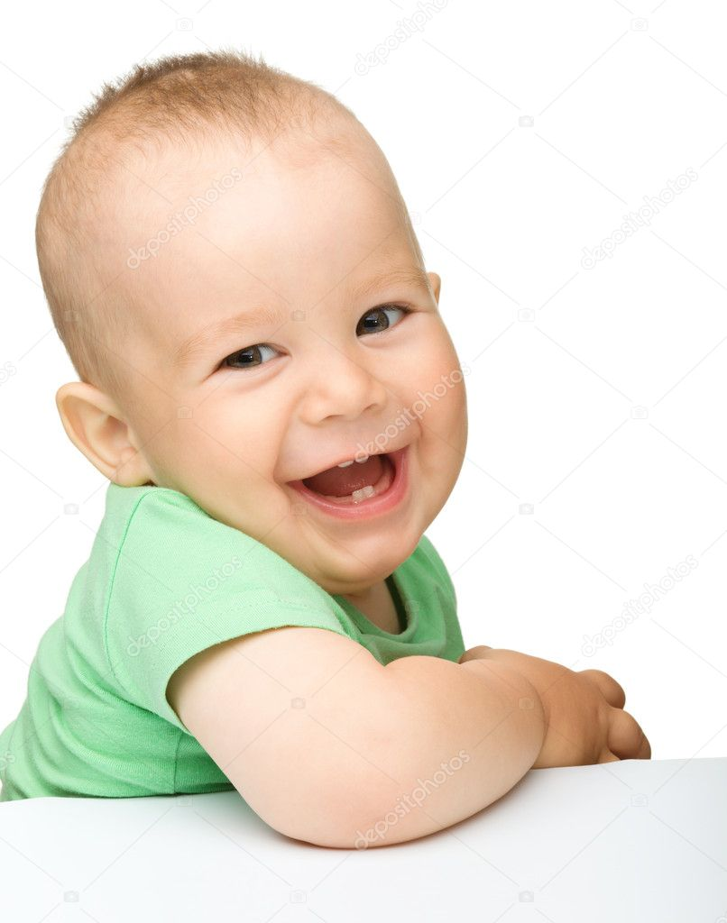 Portrait of a cute cheerful little boy, who is smiling while sitting at table, isolated over white — 图库照片 #6005652