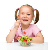 Cute little girl eats vegetable salad — Stock Photo