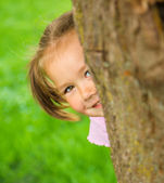 Little girl is playing hide and seek outdoors — Stock Photo