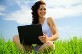 Cute girl is sitting on green grass with laptop — Стоковое фото
