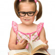 Little girl is flipping over pages of a book — Stockfoto