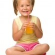 Little girl drinks orange juice — Stock Photo