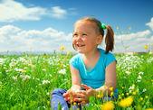 Küçük kız yeşil çayır üzerinde oynuyor — Stok fotoğraf