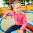 Cute little girl is riding on merry-go-round — Stock Photo
