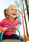 Cute little girl is swinging on see-saw — Stock Photo