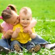 Two children are sitting on green meadow — Stock Photo