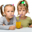 Two little girls are drinking orange juice — Stock Photo #6290485