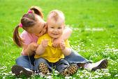 Dos niños están sentados en el prado verde — Foto de Stock