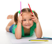 Little girl is drawing while laying on the floor — Stock Photo