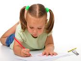 Dziewczynka jest rysunek podczas układania na podłodze — Zdjęcie stockowe