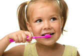 Little girl is cleaning teeth using toothbrush — Stock Photo
