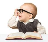 Malé dítě hrát s knihou a brýle — Stock fotografie