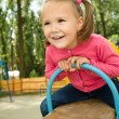Cute little girl is swinging on see-saw — Stock Photo #6581606