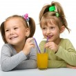 Two little girls are drinking orange juice — Stock Photo #6588049