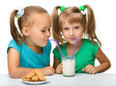 Two little girls are drinking milk — Stock Photo