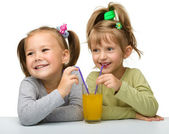 Two little girls are drinking orange juice — Stock Photo