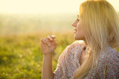 Girl is relaxing on green field — Stock Photo