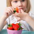 LIttle girl eating strawberries — Stock Photo