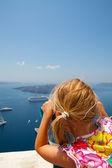Girl looking with binoculars in Thira, Santorini, Greece — Stock Photo