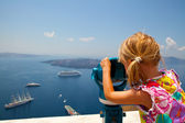 Girl looking with binoculars in Thira, Santorini, Greece — Stock Photo