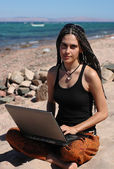 Girl with laptop on a beach — Stock Photo