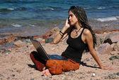 Dizüstü bilgisayar ve cep telefonu bir plajda kız — Stok fotoğraf