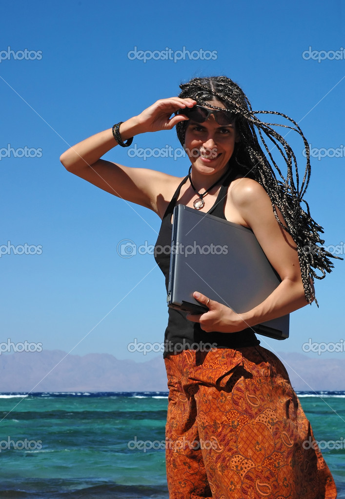 This young woman can be a professional freelancer or a student studying outdoors. She stands on a beach with her laptop. — Stock Photo #5448102
