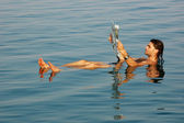 Man floating in a dead sea with newspaper — Stock Photo