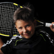 Tennis boy smiling isolated in black — Stock Photo
