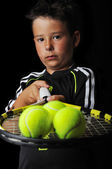 Tennis boy holding balls isolated in black — Stock Photo