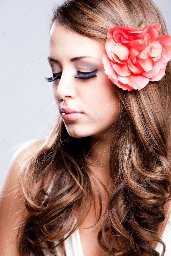 Young brunette woman beauty portrait, flower in hair, profile, studio shot — Stock Photo #5471875