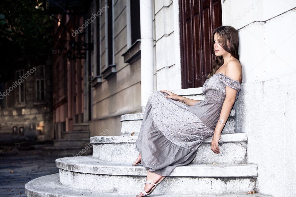 Young woman in summer dress sit on stairs, waiting for someone, outdoor shot — Stock Photo #6467967
