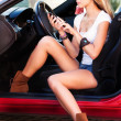 Woman in car with mobile phone — Stock Photo