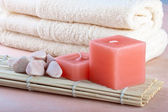 Red candles and towel with peach background — Stock Photo