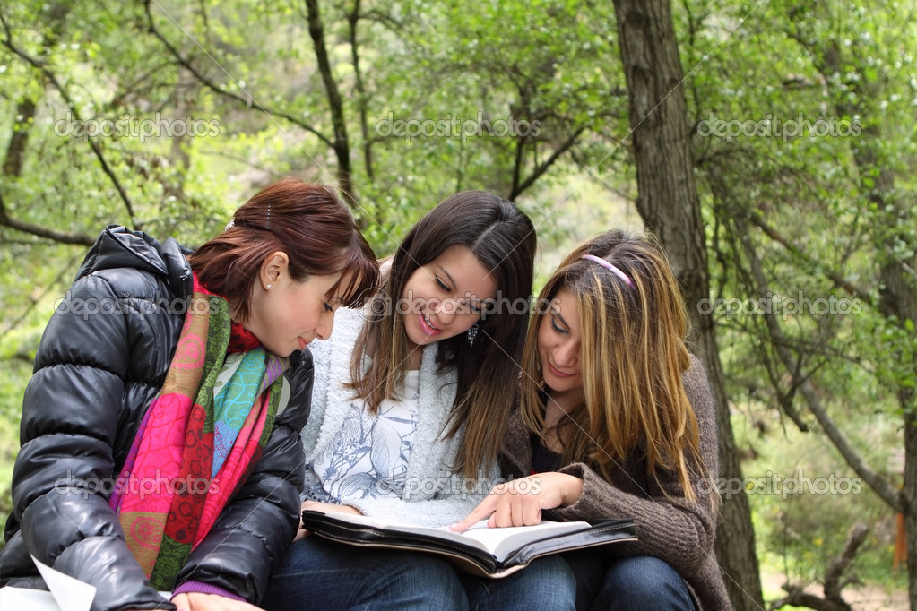 Three girls sitting in forest reading together — Stock Photo #5608286